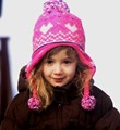 Happy young girl playing outside on a cold snowy day, very proud of her new hat.