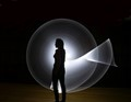 A regular flashlight is moved in a circle motion behind the model.
