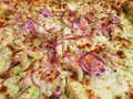 Photo of chicken and onion pesto pizza carry out.  Photo taken at home before eating.