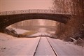 Carondelet Park, in Saint Louis, Missouri, USA - railroad track and bridges, at night, in the snow