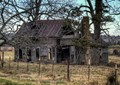 Abandoned and derelict farmhouse in north west Arkansas, USA. Taken from a moving car.