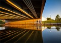 In the light of the Golden Hour, two people navigate a sidewalk-puddle coming out from under a bridge in Chicago's Humboldt Park.