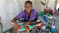 Haitian boy resting on motorcyle