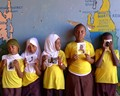 Children from a class in literacy through photography.  They are showing self-portraits where they were asked to act out a feeling.