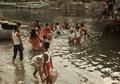 People plunge in the dirty water of rivulet Buri Ganga,flowing beside Kolkata's venerable Kalighat Temple,India,unthinkable in West concept.