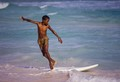 "Young boy ""surfing on a broken surfboard at Silver Rock Beach in Barbados. Photo taken Jan. 1986 Digitized slide(Canon 6D/ 60mm nikkor)"