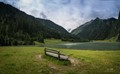 A lonely bench at a mountain lake, somewhere amidst the Alps