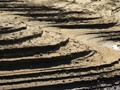 Terraces of sand form on the shore of an artificial lake as the water recedes in late summer.