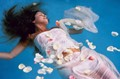 model floating in pool with rose petals