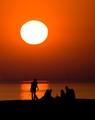 A picnic at the beach Malmö Sweden with the sun setting over Copenhagen.