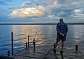 Early evening photo of a fishing friend as he quietly stood on the dock where we were staying on Lake Gogebic, Michigan UP waiting for a bite. The stillness was unusual on this often windy lake.