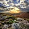 Stormy Skies: After a morning of heavy rain the sun broke through the clouds. A view towards Higger Tor at the top of the Burbage Valley in the Derbyshire Peak District, UK.