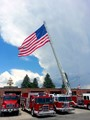 """Following the Independence Day parade in Cody, Wyoming, the Volunteer Fire Department displays their huge """"Stars And Stripes"""" from the end of the """"tele-squirt"""" truck, parked in front of the fire hall."""