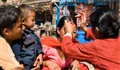 Affixing a Tika mark on woman's forehead,  Swayambhunath Temple, in Kathmandu