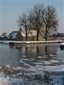 Frozen  canal with snowy dyke house.