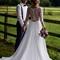 Hochzeitspaar an der Pferdekoppel: Brautpaar steht am Zaun einer Pferdekoppel