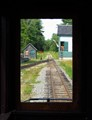 A view of the water tower at the Wiscasset, Waterville & Farmington railway in Maine.  Taken from a wooden coach.