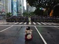 Protester sits in the middle of the street against  raises on public transport fares