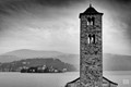 The ancient bell tower of the romanic church of Pella, Italy, with San Giulio island in the Orta lake