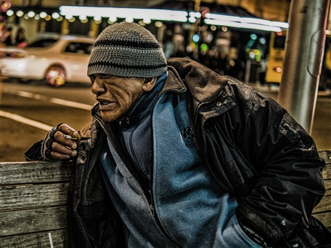 Man Sitting on Street Bench