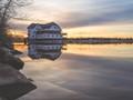 The Ottawa New Edinburgh Club Boathouse during sunset over the Ottawa River.