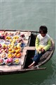 Child on boat selling fruits