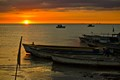Sunset is the backdrop as these fishing vessels rest for the evening after a day of fishing activities.