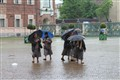 A group of nuns arriving at the Cathedral of Saint John the Baptist in Turin, Italy, on a rainy day.